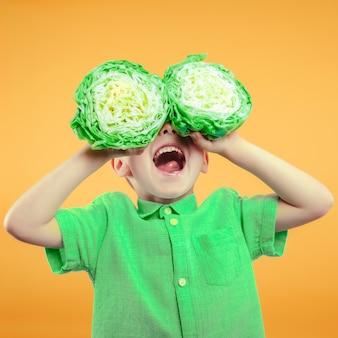Szczęśliwy ładny chłopiec bawi się z zieloną kapustą na żółtej ścianie powierzchni. jasne zdjęcie chłopca. kolorowe zdjęcie panoramiczne.