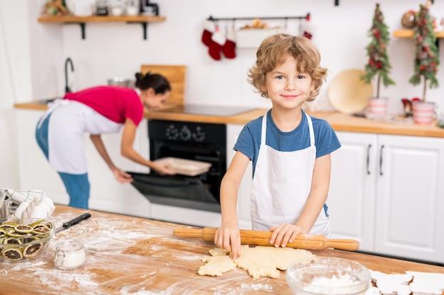 Szczęśliwy ładny chłopiec w fartuch stojący przy kuchennym stole i pomagający swojej mamie zrobić ciasteczka na boże narodzenie