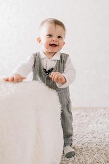 Szczęśliwy ładny chłopiec w garniturze dżentelmena stoi w pobliżu wsparcia na jasnym tle