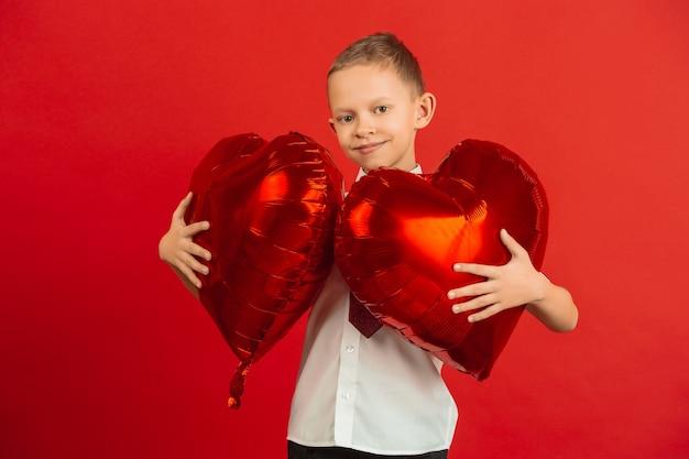 Szczęśliwy, ładny kaukaski chłopiec na białym tle na czerwonym studio