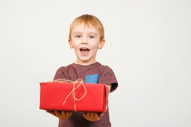 Szczęśliwy ładny małe dziecko trzymając czerwone pudełko na białym tle nad białym tle.