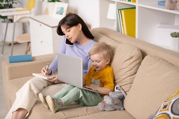 Szczęśliwy ładny mały chłopiec bawi się z laptopem siedząc na kanapie obok swojej młodej matki, rozmawiając na smartfonie i robiąc notatki w notatniku