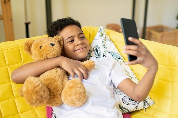 Szczęśliwy ładny mały chłopiec pochodzenia afrykańskiego ze smartfonem obejmującym swojego misia, siedząc na żółtej kanapie i robiąc selfie
