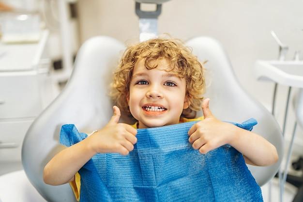 Szczęśliwy ładny mały chłopiec w gabinecie stomatologicznym pokazując kciuki do góry po leczeniu.