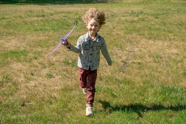 Szczęśliwy ładny mały chłopiec z blond kręconymi włosami, trzymając zabawkowy samolot i spływający zielony trawnik w naturalnym środowisku w letni dzień