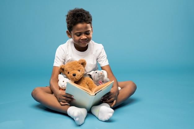Szczęśliwy ładny mały chłopiec z dwoma miękkimi zabawkami i misiem uśmiecha się do ciebie podczas gry w studio przed kamerą na niebiesko