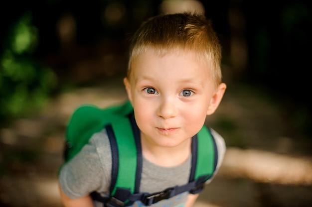 Szczęśliwy ładny mały chłopiec z zielonym plecakiem