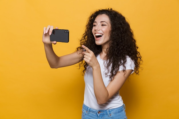 Szczęśliwy ładny młoda kobieta pozowanie na żółtym tle weź selfie przez telefon komórkowy.