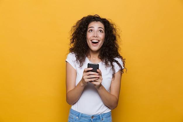 Szczęśliwy ładny młoda kobieta pozowanie na żółtym tle za pomocą telefonu komórkowego.