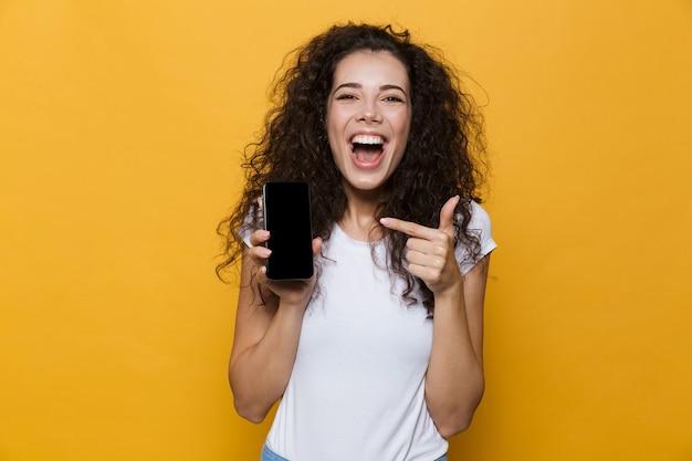 Szczęśliwy ładny młoda kobieta pozuje na białym tle na żółtym pokazie wyświetlacza telefonu komórkowego.