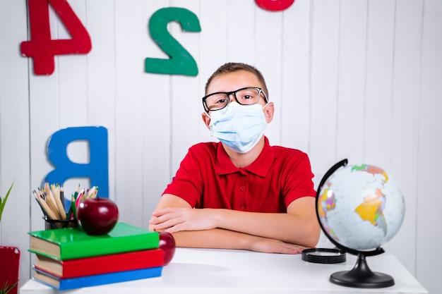 Szczęśliwy ładny sprytny chłopiec siedzi przy biurku w okularach z podniesioną ręką. dziecko jest gotowe odpowiedzieć tablicą