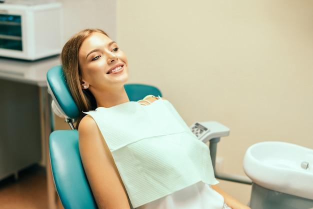 Szczęśliwy ładny żeński pacjent w stomatologicznym biurze.