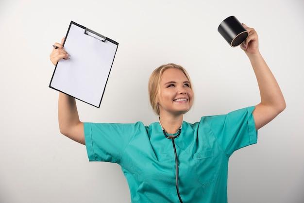 Szczęśliwy lekarz trzymając schowek i kubek na białym tle.