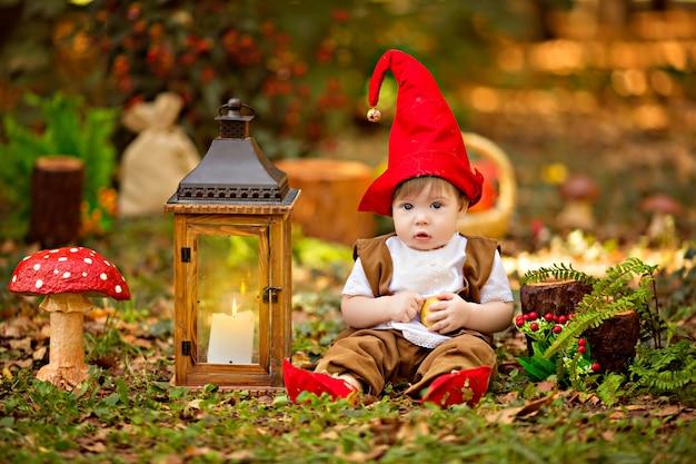 Szczęśliwy leśny krasnal bawi się i spaceruje po lesie, zbiera i zjada pyszne jabłka