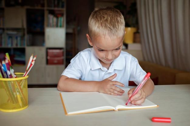 Szczęśliwy leworęczny chłopiec piszący w papierowej książce lewą ręką międzynarodowy dzień leworęczny