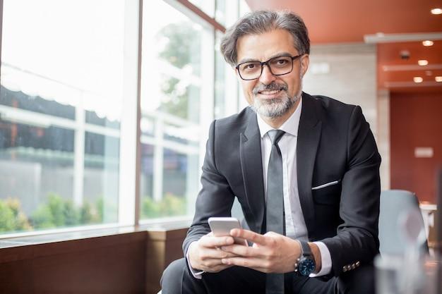 Szczęśliwy lider biznesu korzystanie z smartphone w lobby