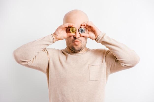 Szczęśliwy łysy biznesmen bawić się z bitcoin monetami przed oczami. blockchain śmieszny górnika portret odizolowywający na bielu