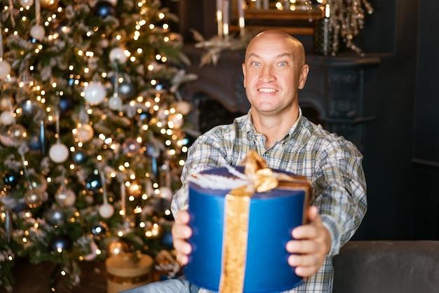 Szczęśliwy łysy mężczyzna w koszuli trzymający niebieskie pudełko z prezentem na tle choinki