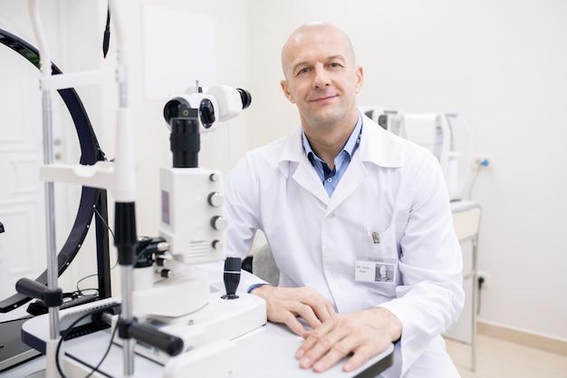 Szczęśliwy łysy okulista w średnim wieku w białym fartuchu siedzi przy miejscu pracy przy sprzęcie medycznym w swoich klinikach