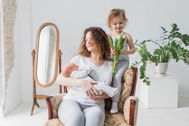 Szczęśliwy macierzysty obsiadanie na ręki krześle z jej ślicznym dwa dzieckiem w domu