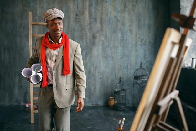 Szczęśliwy malarz mężczyzna z rolkami płócien pozuje przy sztalugach w pracowni artystycznej. artysta blisko swojego miejsca pracy, kreatywny mistrz pracuje w warsztacie