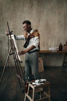 Szczęśliwy malarz przygotowuje sztalugi z płótna w pracowni artystycznej. mężczyzna artysta rysuje w swoim miejscu pracy, twórczy mistrz pracuje w warsztacie