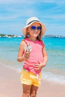 Szczęśliwy małej dziewczynki łasowania lody podczas wakacje na plaży.