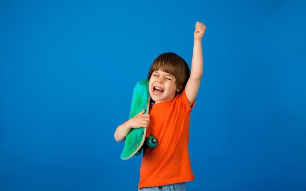 Szczęśliwy maluch chłopiec w pomarańczowej koszulce trzyma deskorolkę na niebieskiej powierzchni z kopią miejsca