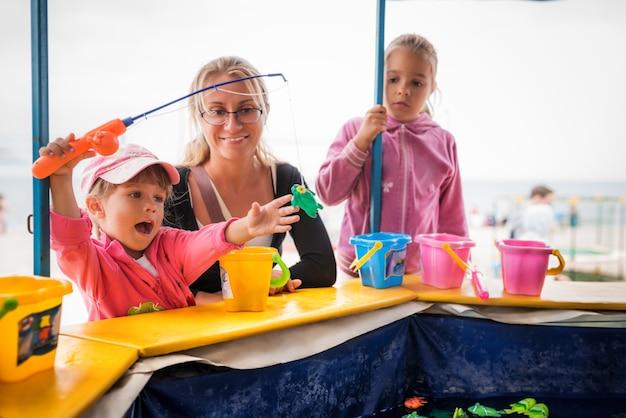 Szczęśliwy maluch dziewczyna z rodziną gra w łowienie ryb. dzieci bawiące się na zewnątrz
