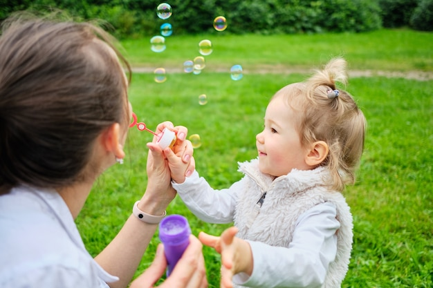 Szczęśliwy maluch i mama robią bańki mydlane w letnim parku