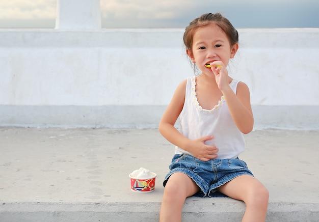 Szczęśliwy mały azjatykci dziewczyny łasowania lody w filiżance plenerowej