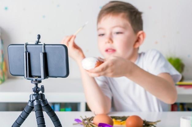 Szczęśliwy mały bloger chłopiec nagrywa strumieniową transmisję wideo na żywo na smartfonie. wielkanocna klasa mistrzowska online dla malowania jajek dla obserwujących. koncepcja blogowania, podświetlenie, selektywna ostrość.