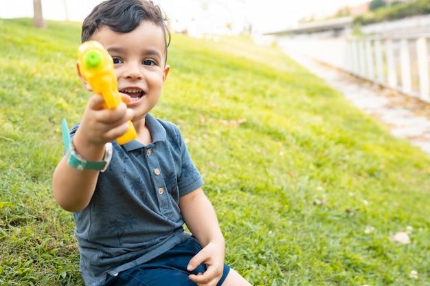 Szczęśliwy mały chłopiec bawi się pistoletem na wodę, koncepcja lato