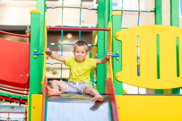 Szczęśliwy mały chłopiec bawiący się na placu zabaw, chłopiec staczający się ze wzgórza, styl życia dzieci