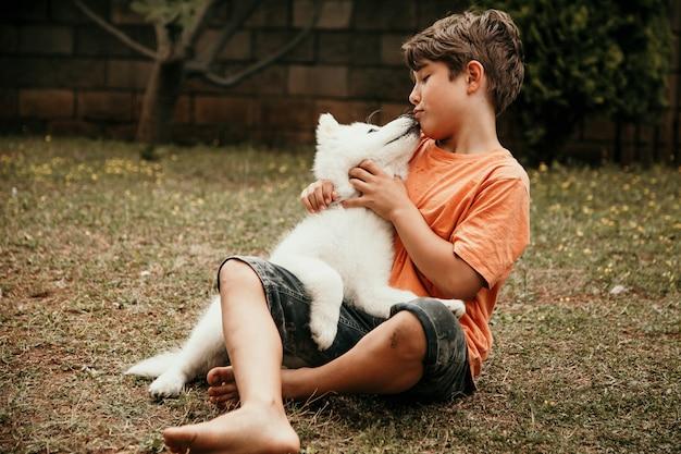 Szczęśliwy mały chłopiec całuje białego psa, trzymając go w ramionach w ogrodzie.