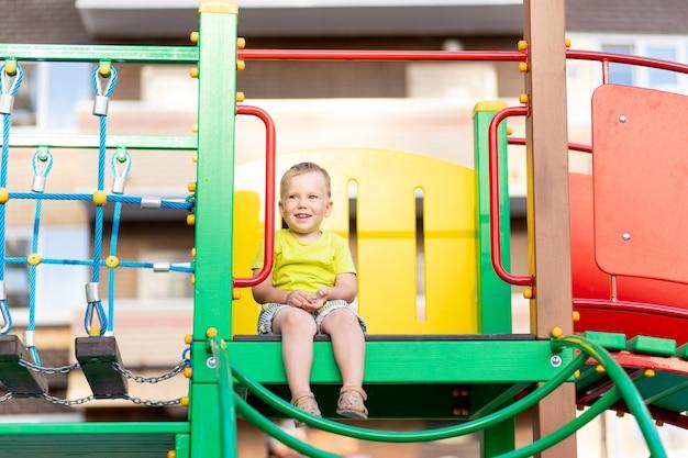 Szczęśliwy mały chłopiec gra na placu zabaw chłopiec toczy się w dół wzgórza
