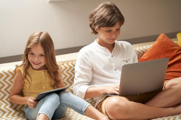 Szczęśliwy mały chłopiec i dziewczynka brat i siostra siedzą na kanapie w domu za pomocą laptopa i cyfrowego