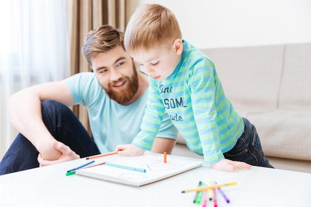Szczęśliwy mały chłopiec i jego ojciec rysują razem w domu