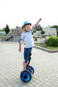 Szczęśliwy mały chłopiec, jazda na hoverboard lub skuter w parku