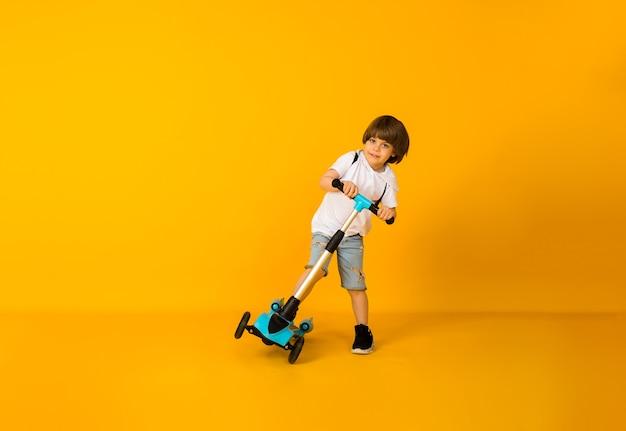 Szczęśliwy mały chłopiec jedzie na skuterze na żółtej powierzchni z miejscem na tekst