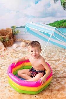 Szczęśliwy mały chłopiec kąpie się w jasnym nadmuchiwanym basenie na piaszczystej plaży z palmami nad morzem