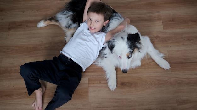 Szczęśliwy mały chłopiec leżący na owczarek australijski