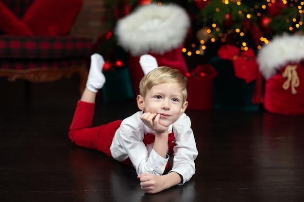 Szczęśliwy mały chłopiec leży na podłodze w pokoju urządzonym na boże narodzenie