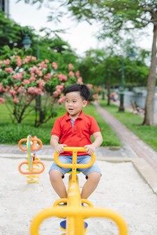 Szczęśliwy mały chłopiec na huśtawce na zewnątrz