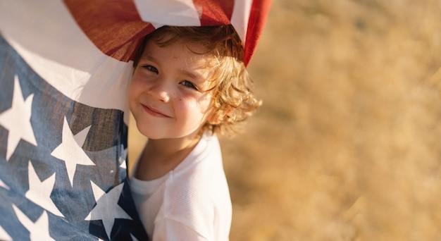 Szczęśliwy mały chłopiec patriota w polu z amerykańską flagą. usa świętują 4 lipca