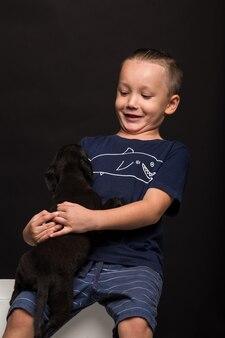 Szczęśliwy mały chłopiec przytulanie szczeniaka na czarnym tle. studio strzał