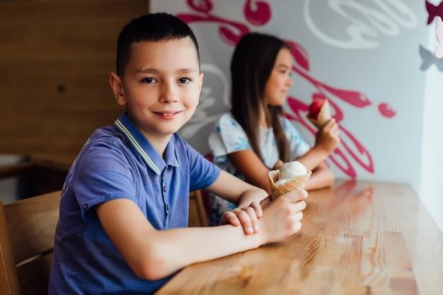 Szczęśliwy mały chłopiec, relaks z lodami w rękach w kawiarni ze swoją dziewczyną.