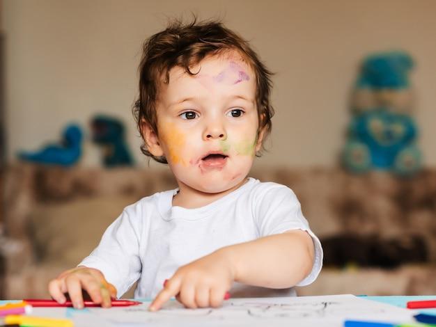Szczęśliwy mały chłopiec rysuje kredkami w albumie