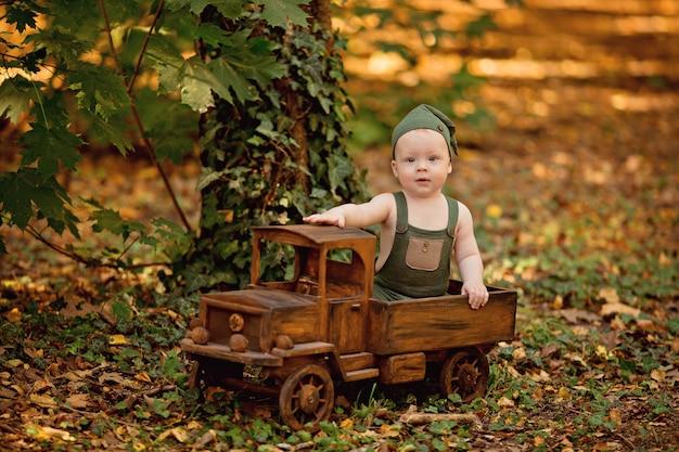 Szczęśliwy mały chłopiec siedzi na zewnątrz w lecie drewniany samochodzik dla dzieci
