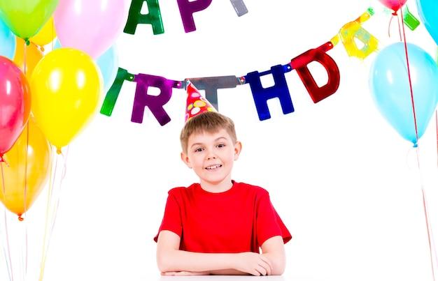 Szczęśliwy mały chłopiec siedzi przy stole zabawy w przyjęcie urodzinowe - na białym tle.
